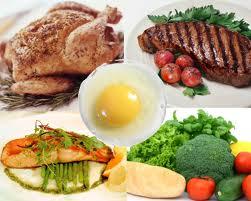 Diversos alimentos con alta cantidad de proteínas, huevos, pollo, filete, salmón y verduras como el tomate y el brócoli
