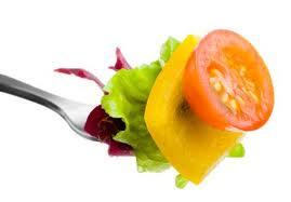 Tenedor pinchando lechuga verde y morada, pimiento amarillo y una rodaja de tomate