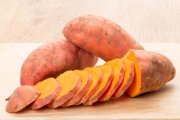 Dos batatas, una sobre la otra y una tercera cortada en rodajas al frente