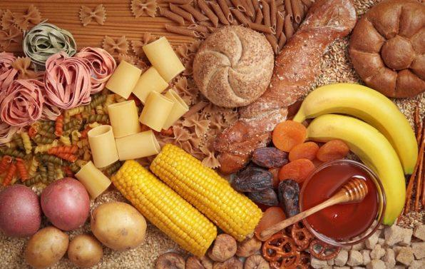 Conjunto de tipos de pasta, mazorcas de maíz, miel, plátanos, pan, patatas y otros alimentos ricos en carbohidratos