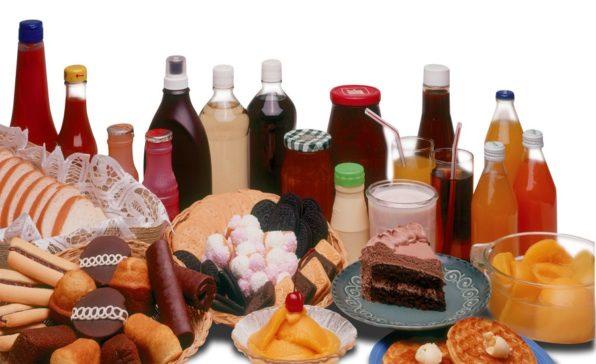Conjunto de botellas de bebidas azucaradas, pasteles, pastas y golosinas como ejemplo de malos carbohidratos