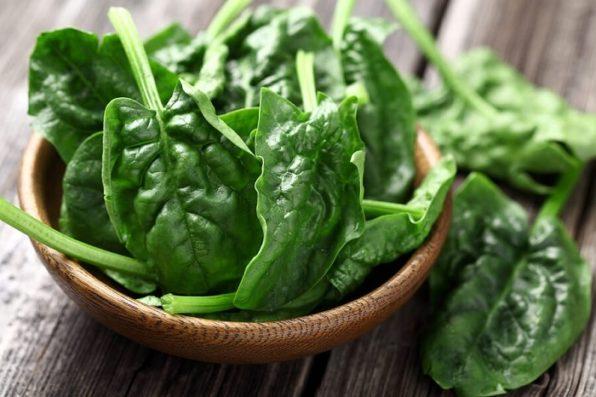 Bol de madera con hojas verdes de espinaca sobre una mesa
