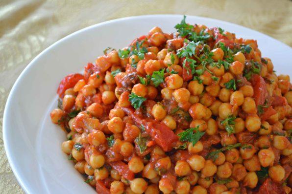 Plato blanco de garbanzos con tomate y perejil