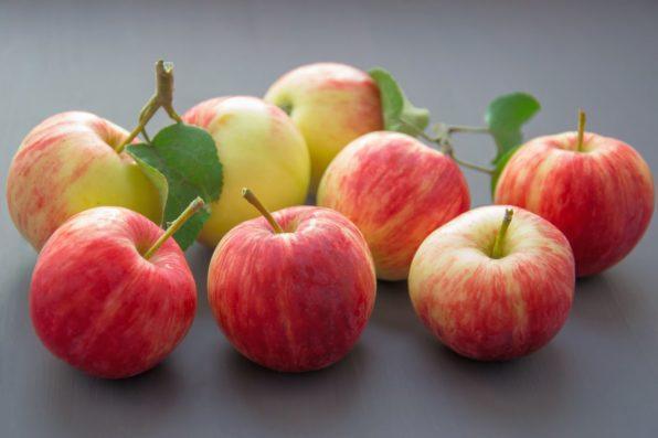 Manzanas rojas sobre una mesa con sus rabos y hojas