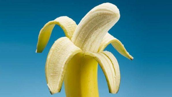 Plátano medio pelado sobre un fondo azul