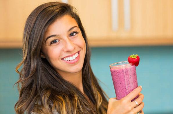 Mujer sonriente con un zumo de frutas en su mano