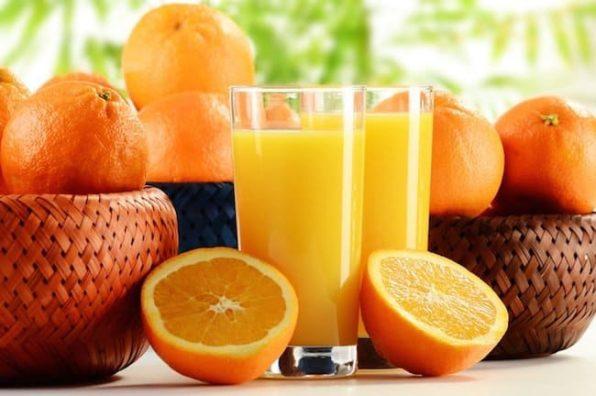 Cestas de naranjas con dos vasos de zumo de naranja