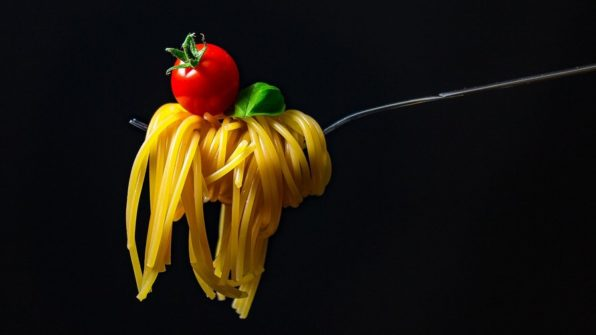 Tenedor con espaguetis enrollados con un tomate encima sobre un fondo negro