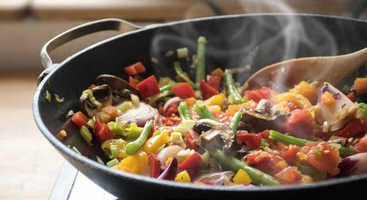 Verduras salteadas en una sartén con cuchara de madera