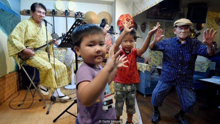 Familia okinawense tocando música y bailando