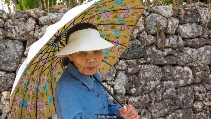 Mujer mayor de Okinawa con una sombrilla para protegerse del sol
